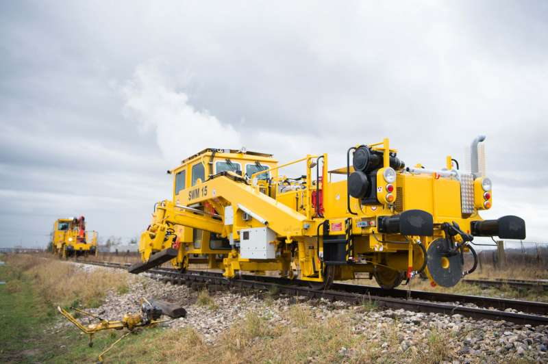The manipulator with the turnable rail gripper deposits the removed sleepers on the ballast shoulder. The OBWSprinter carries out valuable work in the background.