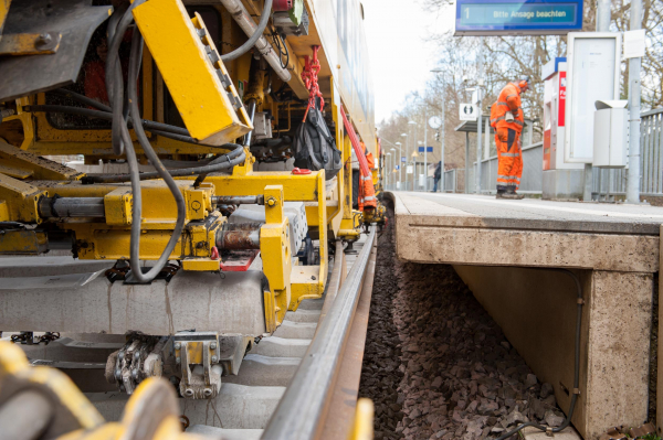The manipulator with the turnable rail gripper deposits the removed sleepers on the ballast shoulder. The OBW Sprinter carries out valuable work in the background.