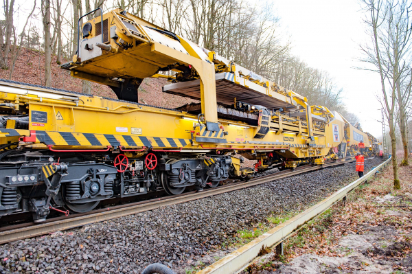 The gantry unit running at the top of the transport wagons can deliver 30 concrete sleepers at a time. Below, the RU 800 S is already collecting the old sleepers for removal.