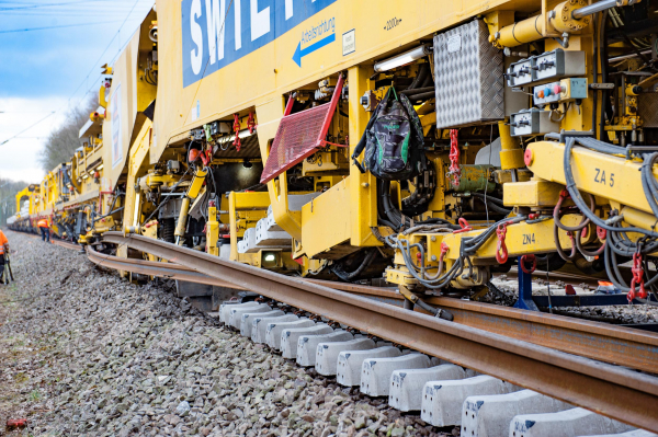 While new sleepers are placed on the ballast formation, the rail guiding clamps guide the long-welded rails from the sleeper ends in a slight curve under the lifted old rail to the rail fastenings.