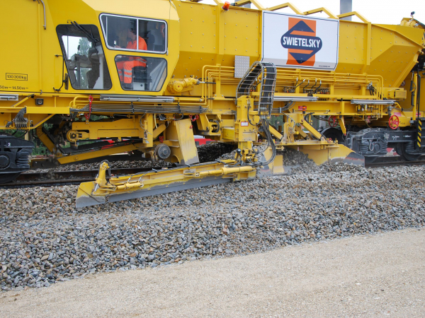 As the machine regulates the track, it picks up and stores surplus ballast.