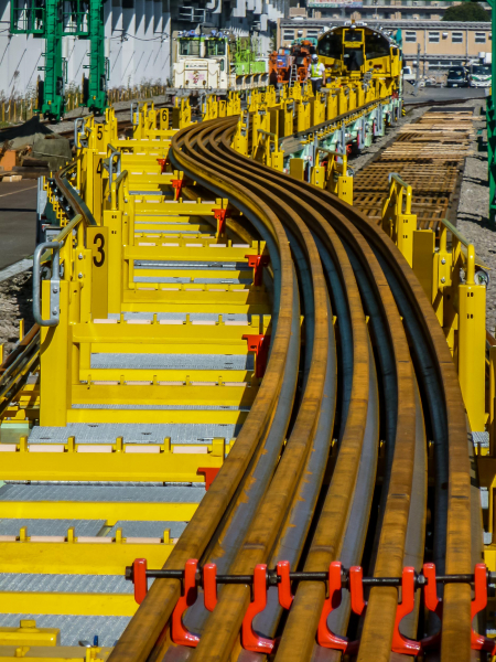 The REX-S can transport up to twenty long welded rails of 150 m length to the work site, where it deposits them next to the track.