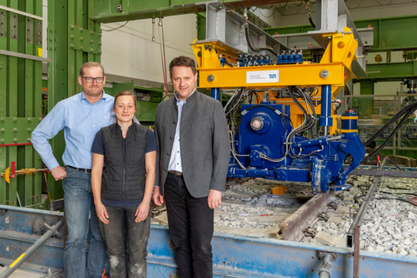 Sophie Feurig with Professor Stephan Freudenstein and Assistant Professor Walter Stahl in front of the test setup at Munich Technical University