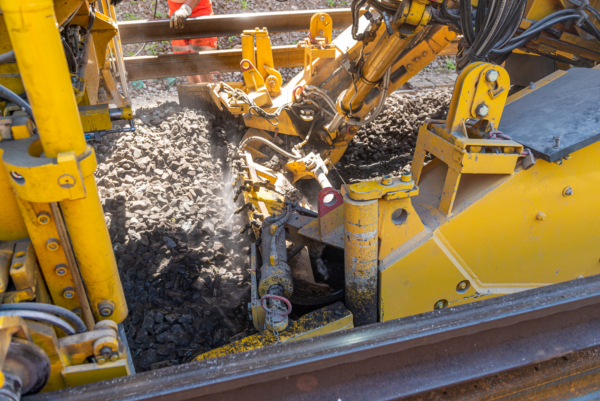 The excavating chain removes the old ballast and creates the perfect base for the new sleepers. The machine can spray water to minimise dust.