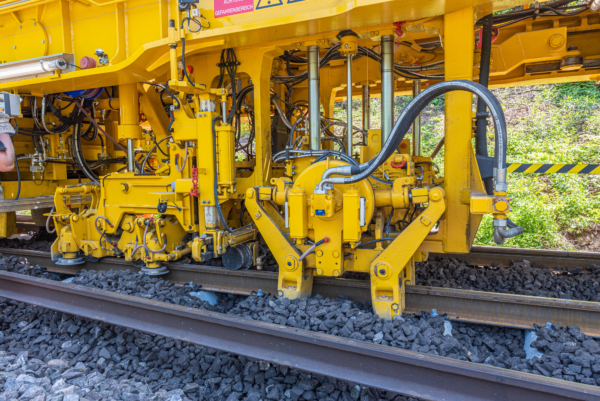 The tamping system with a lifting and lining unit as well as a tamping unit completes the first tamping cycle and fixes the track panel in place.