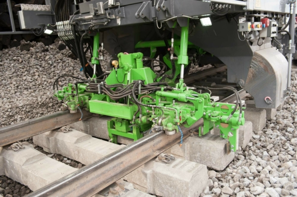 A fixing unit steers the newly laid sleepers to the correctly centred position. Then, it fastens the sleepers to the lifted track.